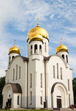 Russian white orthodox church against the blue sky.