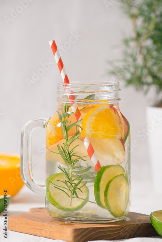 Foto Murales Infused water with lime, orange, apple and rosemary. Cold refreshing detox summer drink .Selective focus