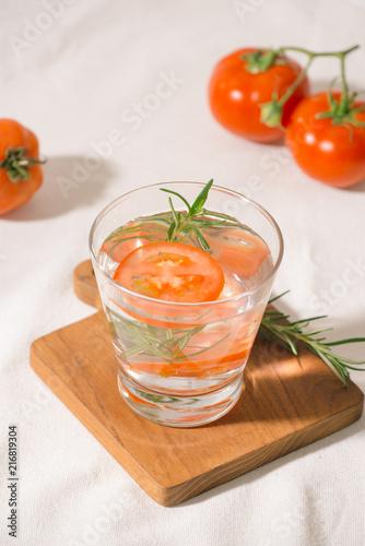 Wyśmienicie odświeżająca woda z rozmarynami i pomidorem w szkle na stole