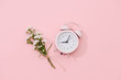 Wildflowers bouquet and retro alarm clock with shadow on pink background