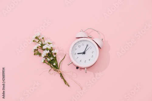 Foto Murales Wildflowers bouquet and retro alarm clock with shadow on pink background