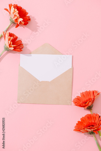 Foto Murales Blank greeting card with brown envelope and gerbera flower on pink table with vintage and vignette tone