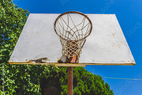 Foto Spatwand Basketbal Basketball hoop against the warm summer sky