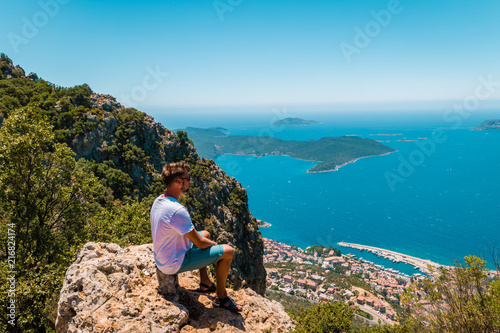 Aluminium Blauwe jeans young man hiking up , Panoramic view from the mountain over the Kas rivera ,hiking up Lycian trail mountain of Kas Turkey