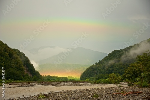 Fotobehang Bleke violet Rainbow in the valley of a mountain river after a summer rain.