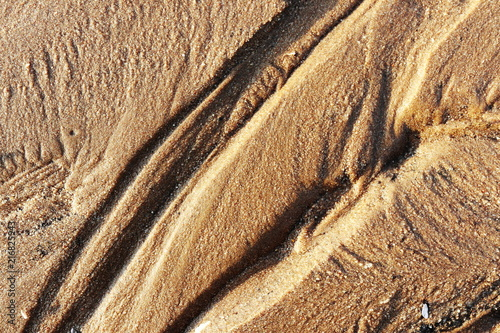 The sand has a trace of water flowing through it.
