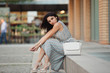 Woman fashion model posing sitting with bag in city