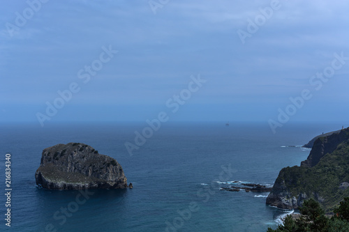 Composition of a little rocky island apart of a rocky coast & the atlantic ocean's horizon at the Basque Country, Spain