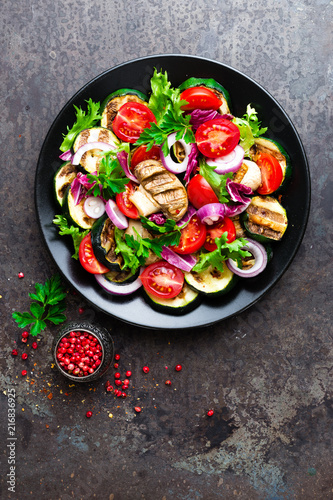 Salad with fresh and grilled vegetables and mushrooms. Vegetable salad with grilled champignons. Vegetable salad on plate. Healthy vegetarian food - 216836925
