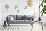 Real photo of a scandi living room interior with cushions on gray couch, cherries on wooden table and bag on a ladder - 216838545