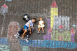 Leinwandbild Motiv Little active kid boy and cute toddler baby girl drawing knight castle and fortress with colorful chalks on asphalt. Happy children with helmet and rocking horse toy having fun with playing knight.