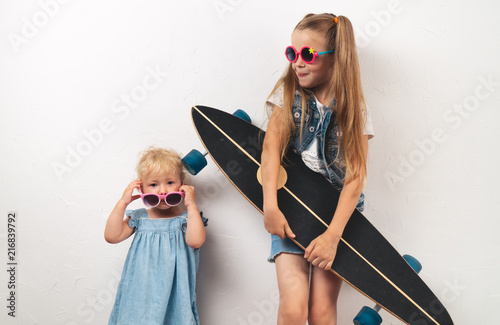 Foto Spatwand Skateboard Two little girls in pink sunglasses and jeans clothes on a white background. The elder sister is holding a long board. Portrait.