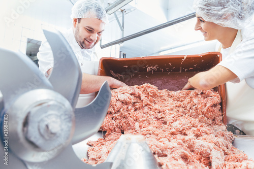 Team of butchers taking minded meat out of grinder machine for further use