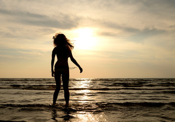 Silhouette of a young woman in sea at sunset.