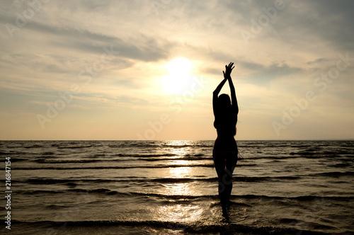 Sylwetka młoda kobieta w morzu przy zmierzchem.