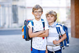 Two little kid boys with backpack or satchel. Schoolkids on the way to school. Healthy adorable children, brothers and best friends outdoors on the street leaving home. Back to school. Happy siblings. - 216849148