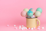 colorful glazed pop cakes and marshmallows in cup over pink background, concept of childrens party