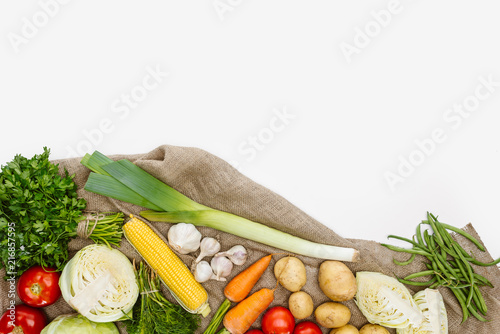 Leinwandbild Motiv food composition with fresh vegetables arranged on sackcloth isolated on white