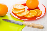 Orange and slices of orange in plate, cutting board, knife