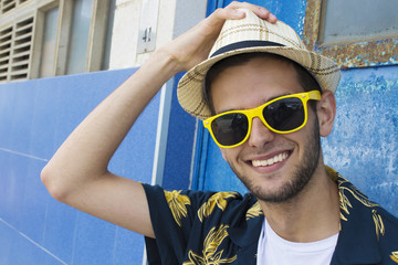 portrait of smiling young man with sunglasses and hat