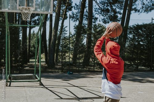 Foto Spatwand Basketbal young man on the basketball court pointing to basket