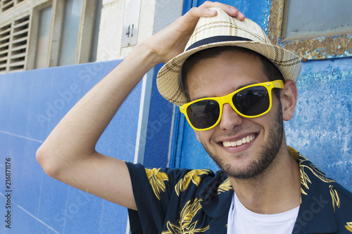 Foto Murales portrait of smiling young man with sunglasses and hat