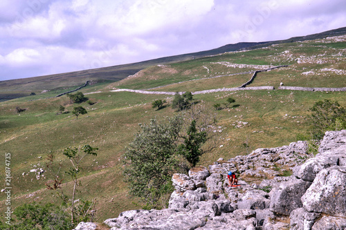 Aluminium Purper Limestone scenery on top of Malham Cove in the Yorkshire Dales National Park. Landscape scene with climber setting up belay rope