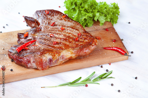 Grilled steak on wooden cutting board on white rustic background. Pork with pepper, hot chili, garlic and rosemary. Isolated on white background. Place for text. Closeup view. Top view. - 216878915