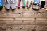 Fitness symbols and equipment - sneakers, water, dumbbell and smartphone with earphones on wooden background