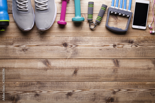 Fototapeta Fitness symbols and equipment - sneakers, water, dumbbell and smartphone with earphones on wooden background