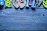 Fitness equipment on wooden background - bottle, dumbbell, jumping rope and sneakers