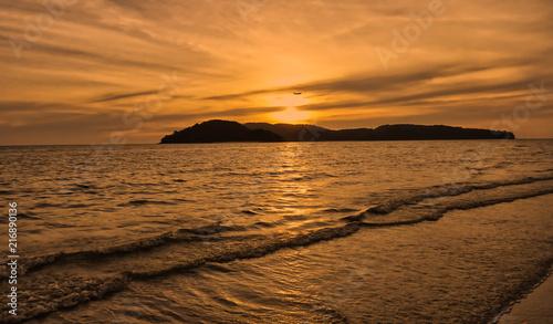 Leinwanddruck Bild Ein Flieger direkt im untergehenden Licht der Sonne am Meer