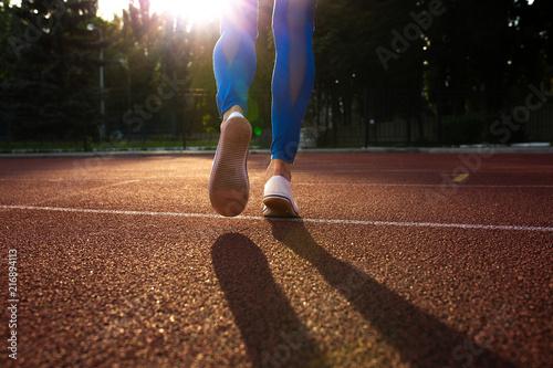 Sport concept. Female runner feet on a track stadium in sun rays