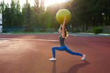 Athletic brunette girl holds fit ball over her head at the stadium in sunny day. Space for text