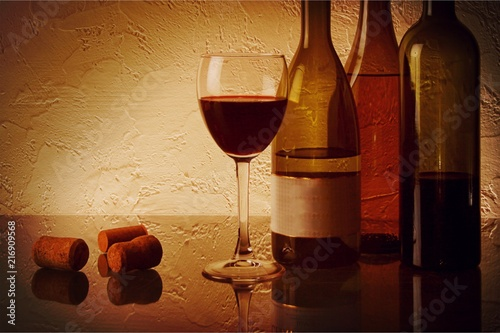 Bottle of wine with grapes on background