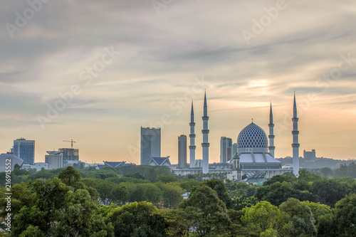 In de dag Kuala Lumpur skyline of Shah Alam city with the view of The Sultan Salahuddin Abdul Aziz Shah Mosque (Blue Mosque), and green tree as foreground. picture taken during sunset moment