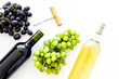 Composition with wine bottles. Red and white wine bottles, bunch of grapes, corkscrew on white background top view space for text