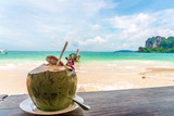 Coconut fruit drink at beautiful Tropical Beach blue ocean background with Traveler items  vacation travel accessories for holiday or long weekend a guide  choice idea for planning travel