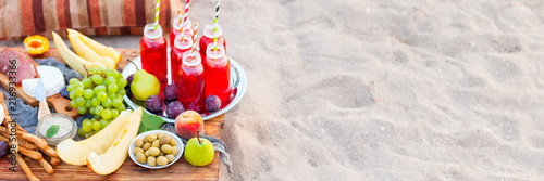 Picnic on the beach at sunset in the style of boho. Concept outdoors evening healthy dinnner with fruit and juice - 216933366