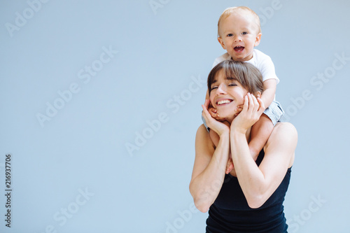Leinwanddruck Bild Happy blond toddler boy laughing on to his sportive mother for a piggyback ride over gray background. Close up portrait. Fitness, happy maternity yoga with children concept.
