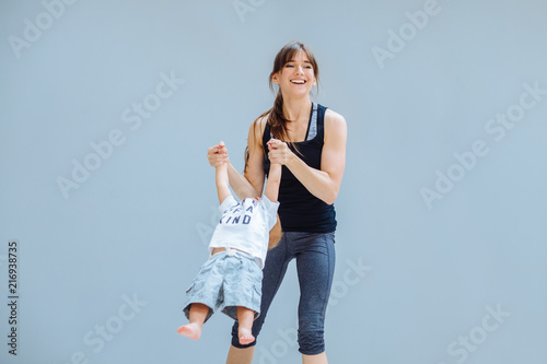 Leinwanddruck Bild Happy laughing mother doing gymnastic for toddler baby boy over gray background at home. Fitness, happy maternity yoga with children concept.