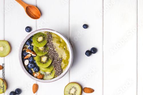 Leinwanddruck Bild Green smoothie bowl with kiwi, blueberry and chia seeds
