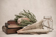 Lovely soft muted tones complement antique books, Australian wildflower and dried tobacco leaf.