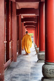 Unknown Buddhist monk walking along red corridor of a temple