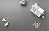 A Gift Box and Christmas Decorations on gray background. Symbolic image. Flatlay. Copy space - 216956552