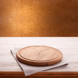 Wooden table with empty board for pizza and tablecloth. Kitchen background top view mock up. Selective focus.