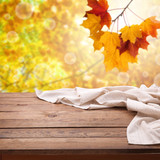 Empty wooden deck table with tablecloth over bokeh autumn leaves background. Kitchen background, product montage display. Mock up . - 216959341