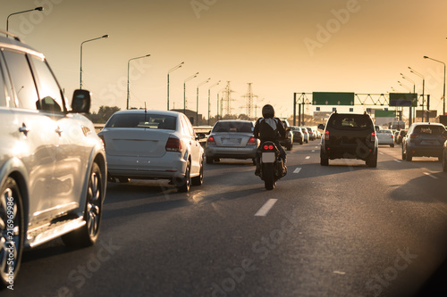 Traffic jam on a hot summer evening. Highway and road junction. Sunset cars and moto - 216969986