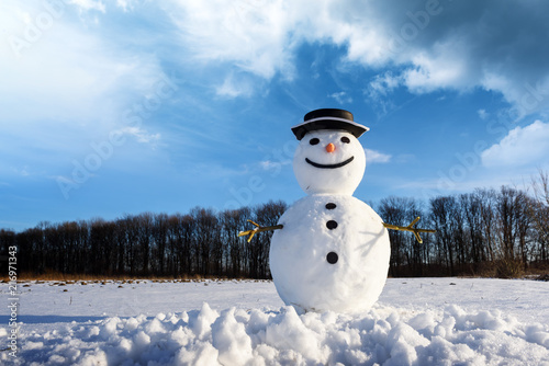 Foto Murales Funny snowman in stylish black hat on snowy field. Merry Christmass and happy New Year!