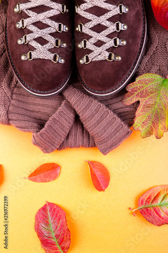 Leinwanddruck Bild Brown man suede boots with sweater on yellow background